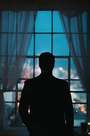 guy standing looking outside window